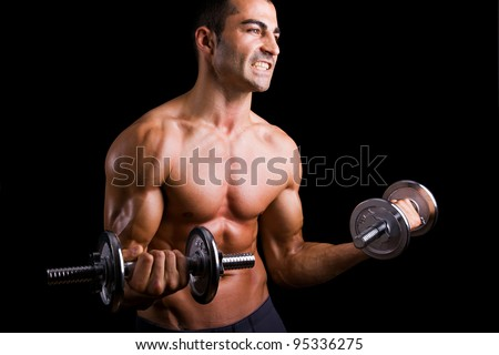 Young man lifting weights on black background