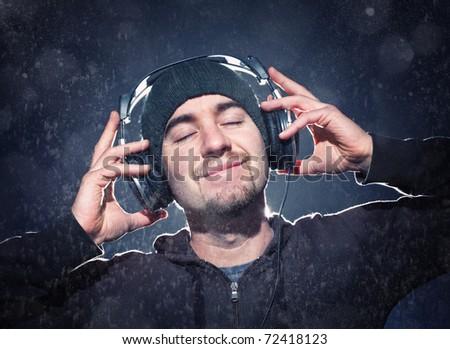 young man listen music with headphone under rain - stock photo