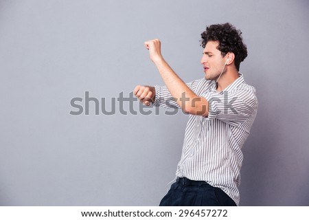 Young man listening music in headphones and dancing over gray background - stock photo