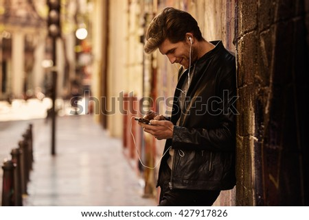 Young man listening music with smartphone earphones in the street - stock photo