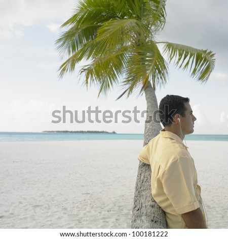 Young man listening to his mp3 player at the beach - stock photo