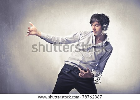 Young man listening to music and playing an invisible guitar - stock photo