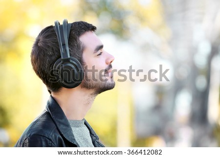Young man listening to music and walking along the street - stock photo