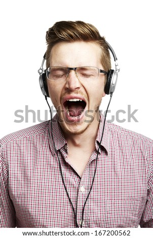 Young man listening to music and yawns. Isolated on white