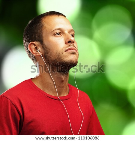 young man listening to music on a green lights background - stock photo