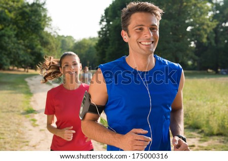 Young Man Listening To Music While Jogging With Woman  - stock photo