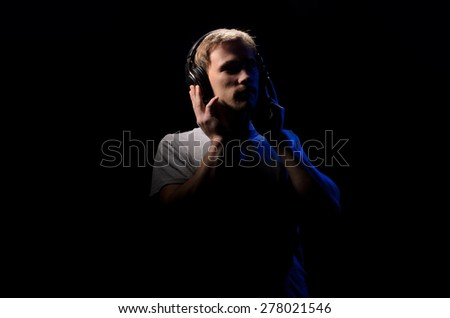 young man listening to music with headphones on black background