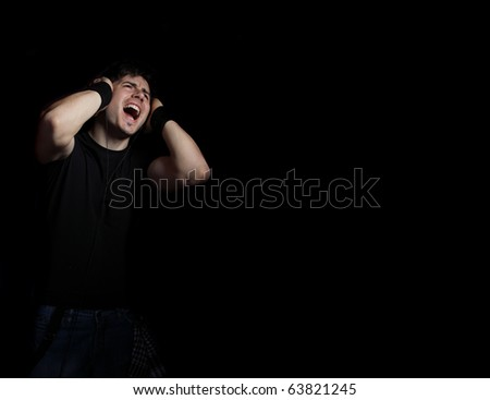 Young Man listening to music with headphones on dark background