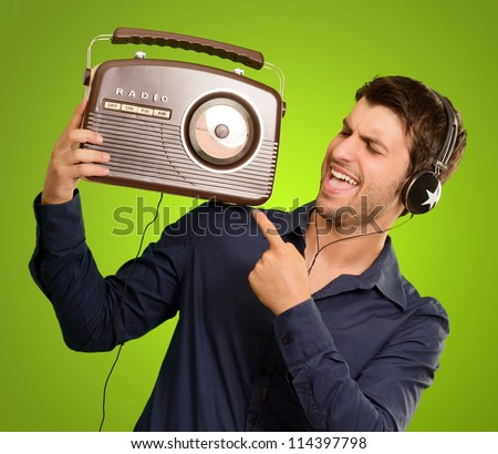 Young Man Listening To Vintage Radio On Green Background