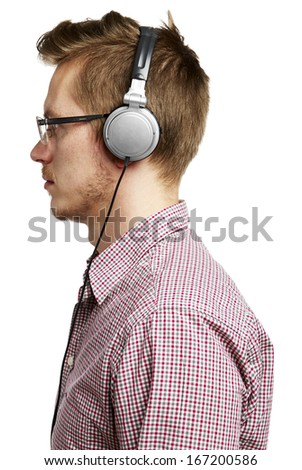 Young man listening with headphones. Isolated on white.  - stock photo
