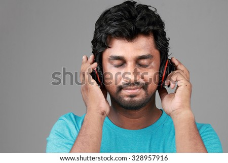 Young man listens music with headphones