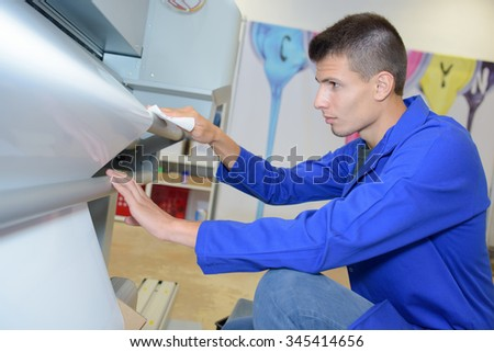 Young man loading new roll into industrial printer - stock photo