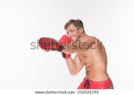 Young man looking aggressive with boxing gloves on. Short-haired man training and posing for photographer isolated on white.