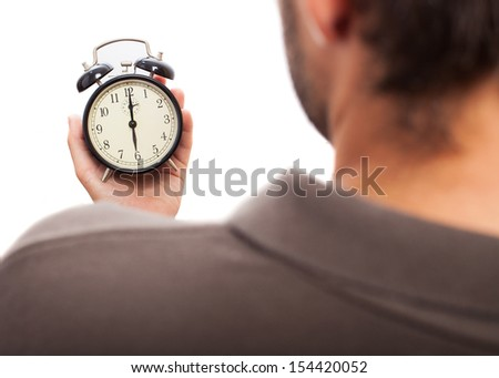 young man looking an alarm clock on a white background