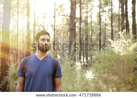 Young man looking around him and listening to the wind in the pine trees of a plantation while wearing casual clothing and a backpack