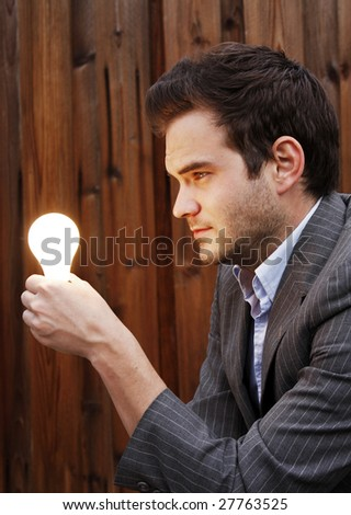 young man looking at a lightbulb in his hand. - stock photo
