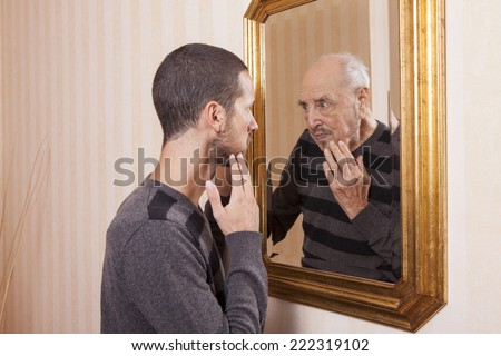 young man looking at an older himself in the mirror - stock photo