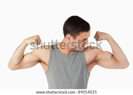 Young man looking at his muscles against a white background - stock photo