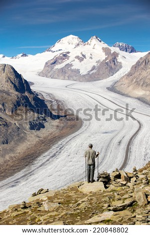 Young man looking at majestic view to Aletsch glacier, the largest gracier in Alps and UNESCO herritage from Eggishorn, Valais, Switzerland, Europe - stock photo