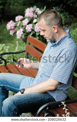 Young man looking at smartphone in the garden - stock photo