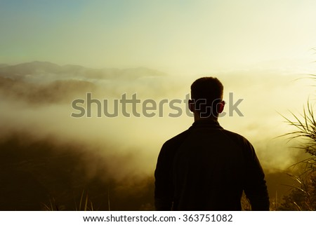 Young man looking at the view from a top a mountain.  - stock photo
