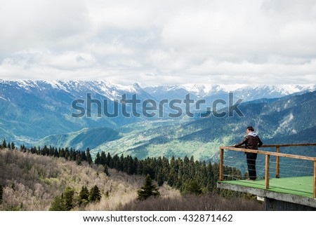Young man looking at the view from a top of mountain. - stock photo
