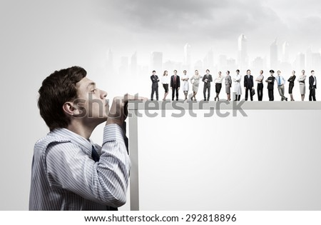 Young man looking from under table on large group of business people - stock photo