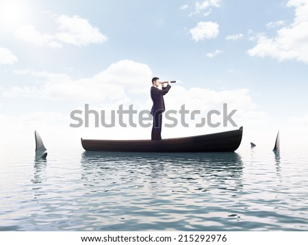 young man looking on boat with sharks around him - stock photo