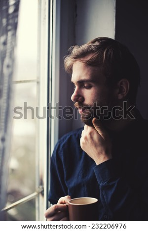 young man looking through a window - stock photo