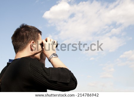 Young man looking through binoculars - stock photo