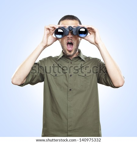 young man looking through binoculars, surprise face expression - stock photo