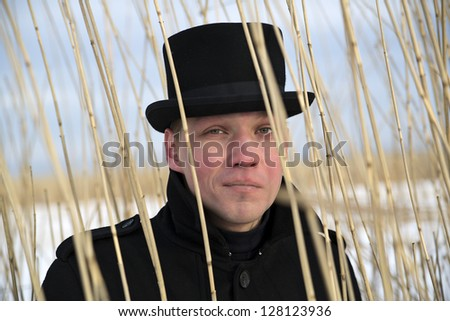 Young man looking through reed brush at winter
