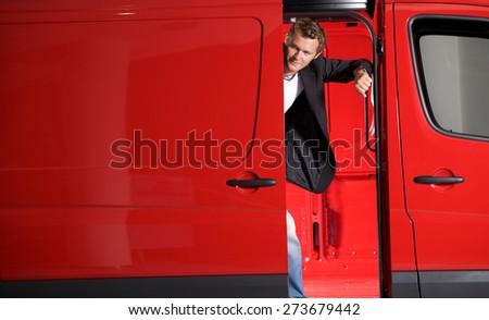 Young man looking through van door - stock photo