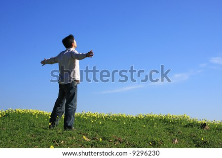 Young man looking to the sky with his arms outstretched - stock photo
