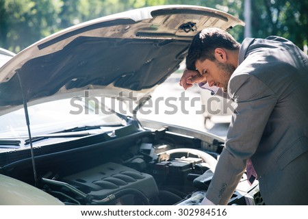 Young man looking under the hood of breakdown car - stock photo