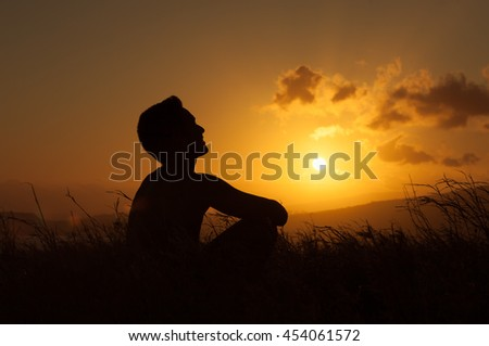 Young man looking up into the sky feeling at peace with nature.  - stock photo