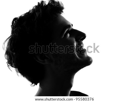 young man looking up portrait silhouette in studio isolated on white background - stock photo