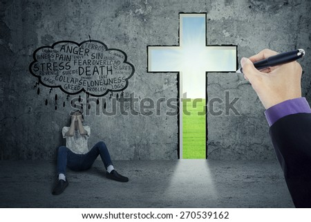 Young man looks depressed, sitting on the floor and lean on the wall near a cross - stock photo