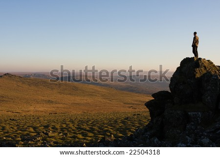 Young man looks over Dartmoor from the top of a rock - stock photo