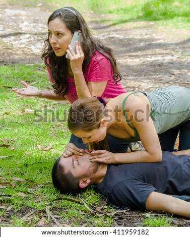 Young man lying down with medical emergency, two young women performing cpr breathing aid, outdoors environment - stock photo
