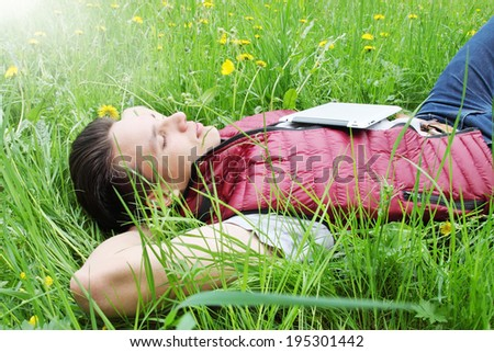 young man lying in the grass with map-case
