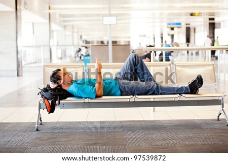 young man lying on airport chairs and resting