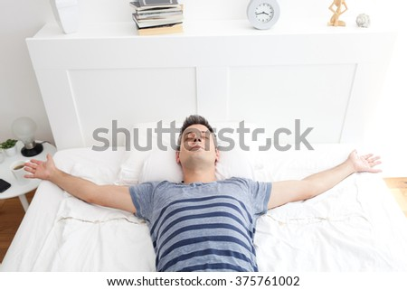 Young man lying on bed, relaxing - stock photo