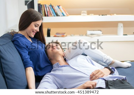 Young man lying on sofa in woman's lap. Happy young couple enjoying spending time together. - stock photo
