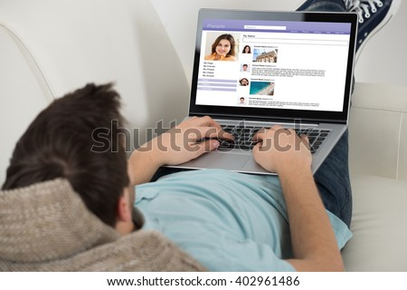 Young Man Lying On Sofa Surfing Social Networking Site On Laptop - stock photo