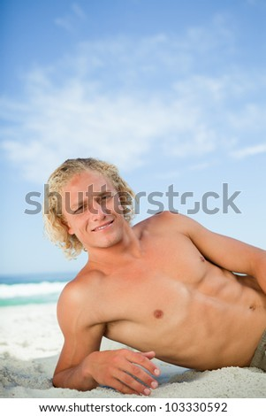 Young man lying on the beach while looking at the camera and showing a great smile - stock photo
