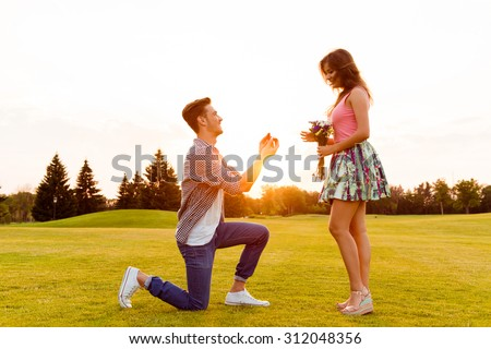 young man makes a proposal of betrothal to his girlfriend - stock photo