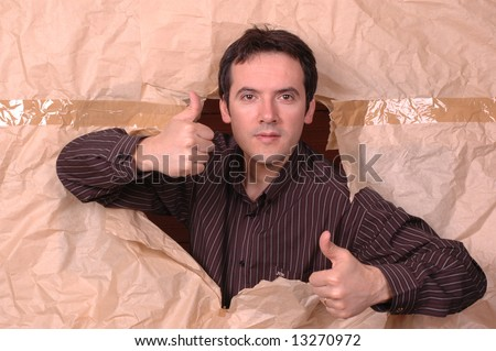 young man making a large hole in paper... - stock photo