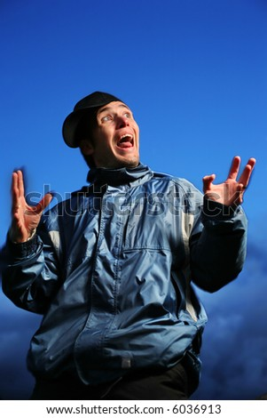 Young man making funny faces at dusk. - stock photo