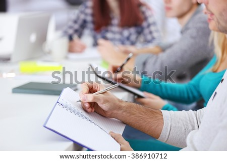 Young man making notes at the office meeting